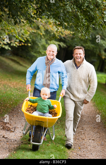 Two men walking on path outdoors pushing baby in wheelbarrow and smiling (selective focus) - Stock-Bilder