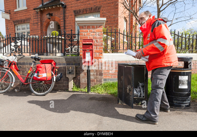 Royal Mail postman collecting mail from a box outside the Old Post Office, Plumtree, Nottinghamshire, England, UK - Stock Image