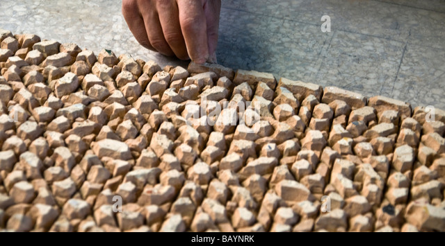 Placing shaped mosaic pieces on pre-designed template. Face down they are covered in concrete then the whole lot - Stock Image