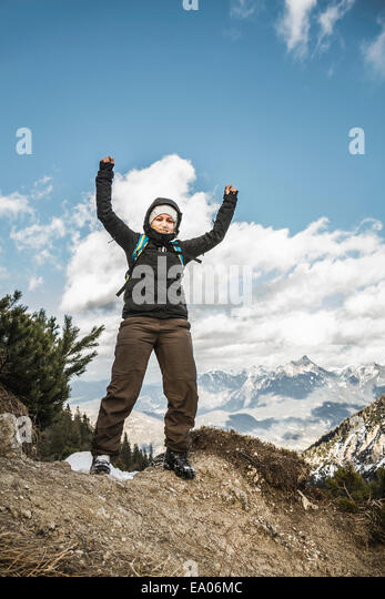 Young woman celebrating on mountain ridge, Hundsarschjoch, Vils, Bavaria, Germany - Stock Image