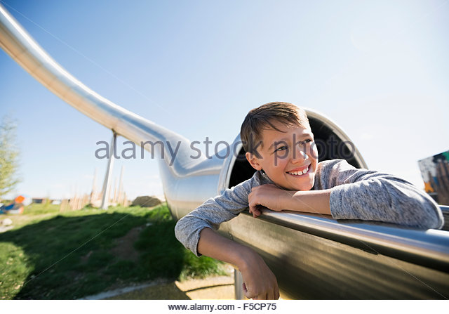 Carefree boy at tunnel slide at sunny playground - Stock Image