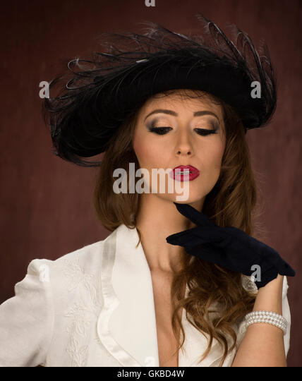 Young brunette woman modeling a vintage black hat - Stock Image
