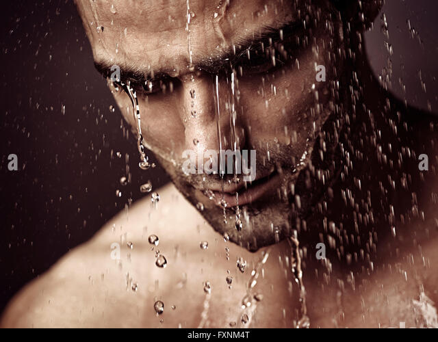 Pensive troubled man's face under shower - Stock Image