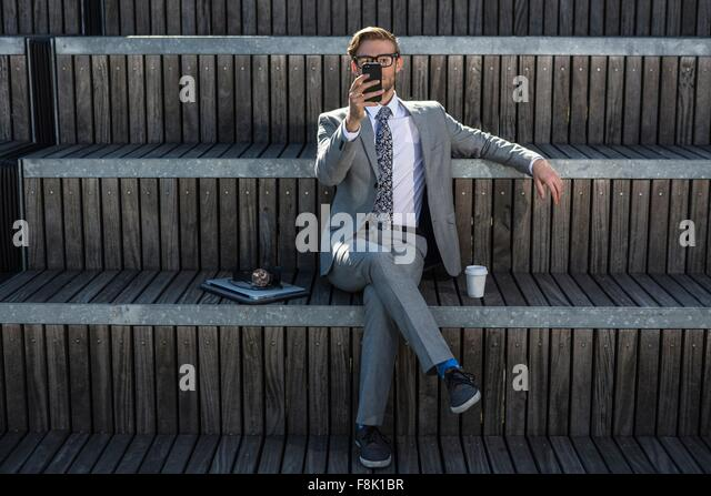 Cool young businessman reading smartphone on city stair - Stock-Bilder
