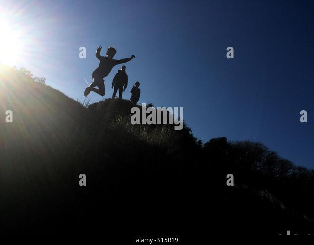 A young boy jumps off a sand dune in front of his brother and sister during a day trip Barafundle Bay in South Wales - Stock-Bilder