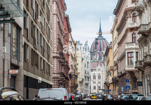 BUDAPEST, HUNGARY - APRIL 7, 2018: Hungarian Parliament (orszaghaz) seen from a nearby street.  It is one of the main touristic landmarks of the city  - Stock Image