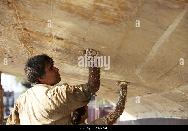 Two workers apply a sealer to the underside of a dhow in the Jaddaf boatyard, Dubai, UAE - Stock-Bilder