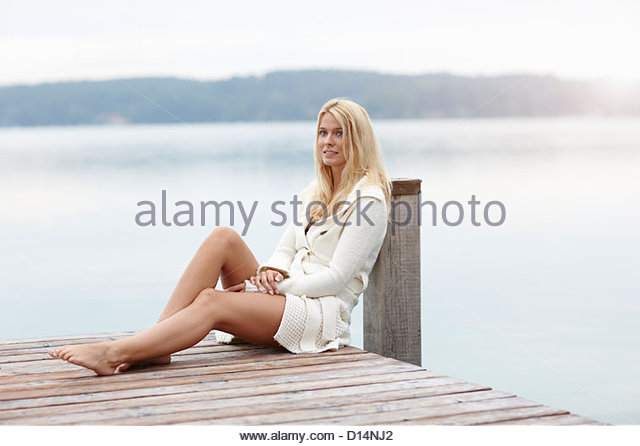 Woman leaning on post on wooden deck - Stock Image