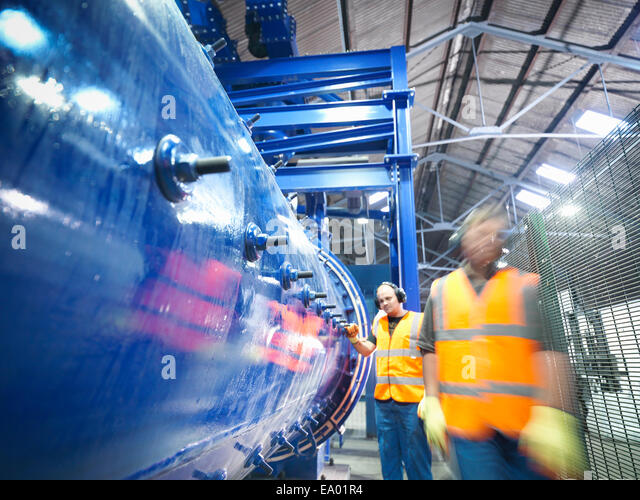 Workers checking metal ore grinding mill - Stock-Bilder