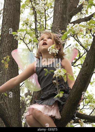 little girl in fairy wings climbing a tree - Stock-Bilder