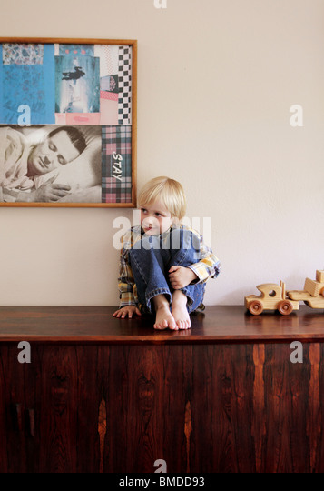 Young boy sitting on shelf - Stock Image