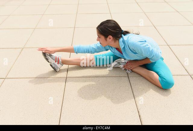 Teenage girl (14-15) stretching - Stock Image