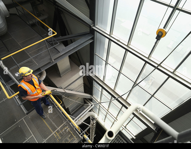 Worker operating machinery in factory - Stock Image