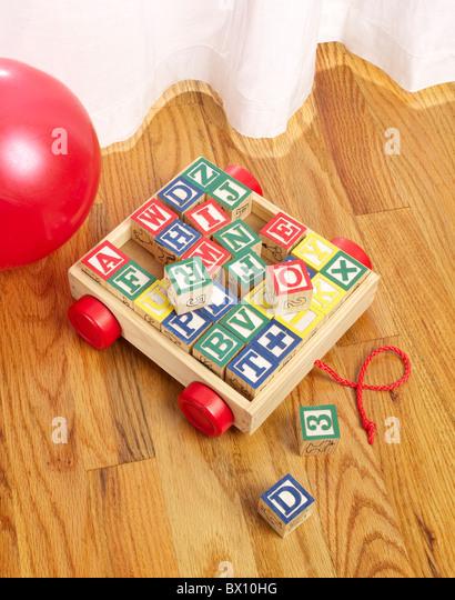 children's wooden blocks on floor vertical - Stock Image