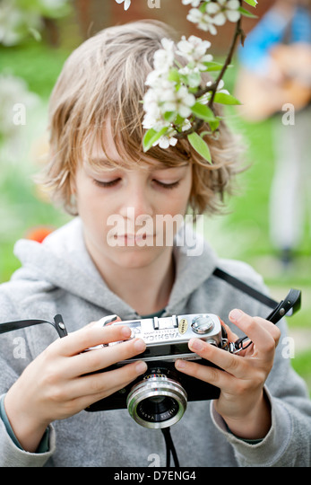 Boy playing with an old camera. - Stock-Bilder