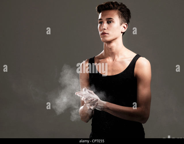 Young athlete rubbing powder on hands against grey background - Stock Image
