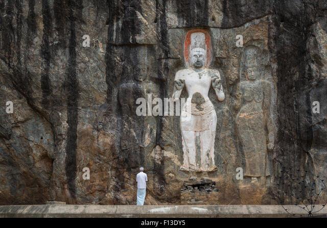 Man worshiping in front of rock sculpture, Sri Lanka - Stock Image