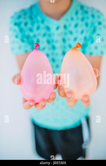 Boy is holding water balloons - Stock Image