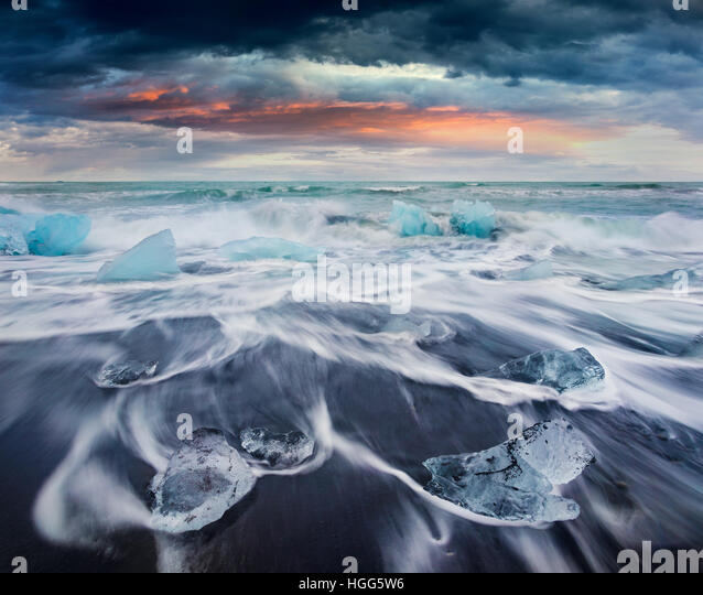 Blocks of ice washed by the waves on Jokulsarlon beach. Dramatic summer sunrise in Vatnajokull National Park, southeast - Stock Image
