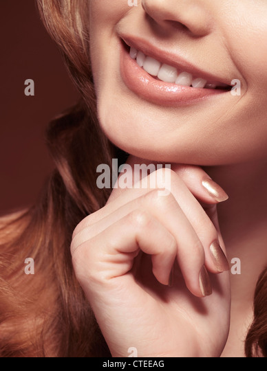 Closeup of mouth of a beautiful young smiling woman - Stock Image