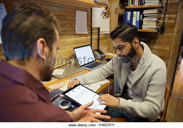 Designers choosing fonts on digital tablet in office - Stock Image