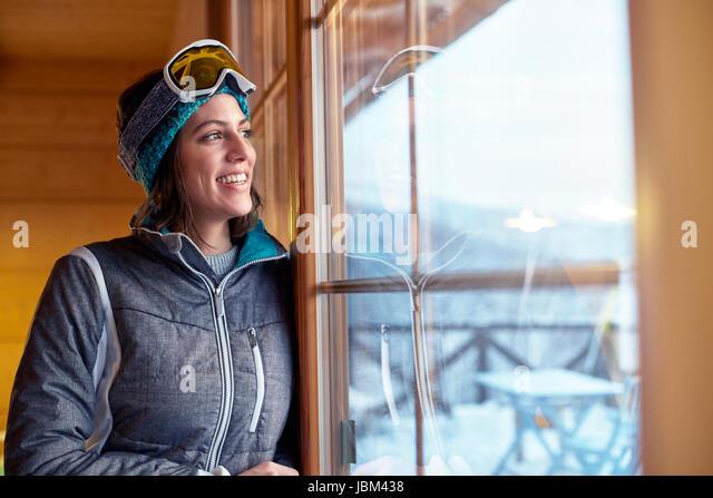 Smiling female skier looking out cabin window - Stock-Bilder