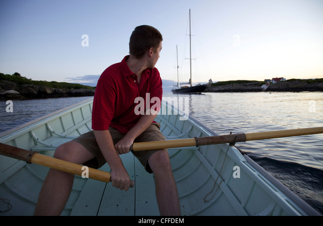 A young man rows in a Peapod dinghy at sunset toward a classic yacht moored along the coast of Maine near Boothbay - Stock Image