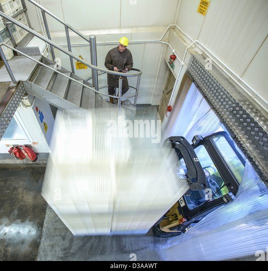 Worker watching fork lift truck in loading bay of food factory - Stock Image