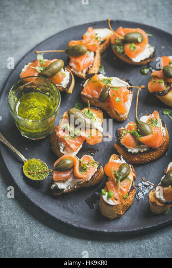 Homemade salmon crostini with cream-cheese, watercress, capers and pesto suace in round black slate stone plate - Stock Image