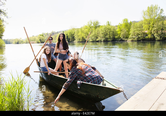 Group of friends in a row boat - Stock Image