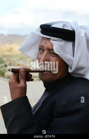 A Bedouin man smoking his cigarette. - Stock Image