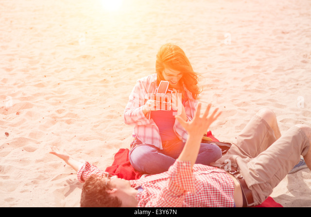 Couple having fun with instant camera on beach - Stock Image