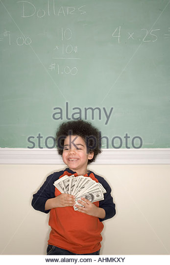 Young African boy holding fake money - Stock Image