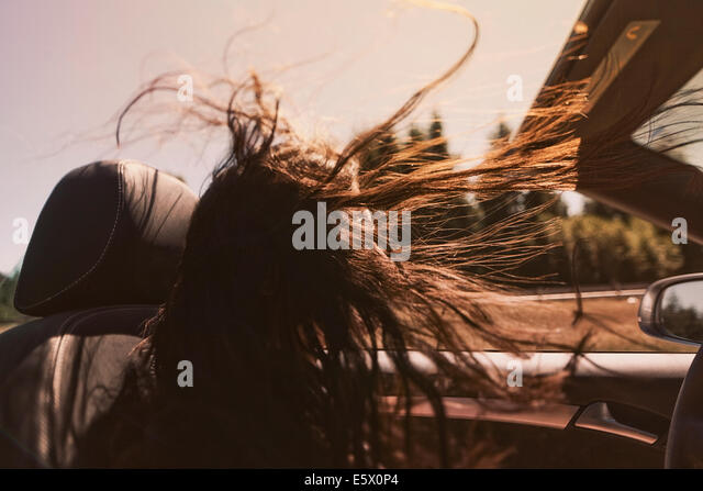 Mid adult woman driving convertible with long hair blowing in wind - Stock Image