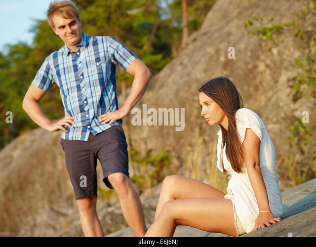 Young couple together, focus on woman and man behind - Stock-Bilder