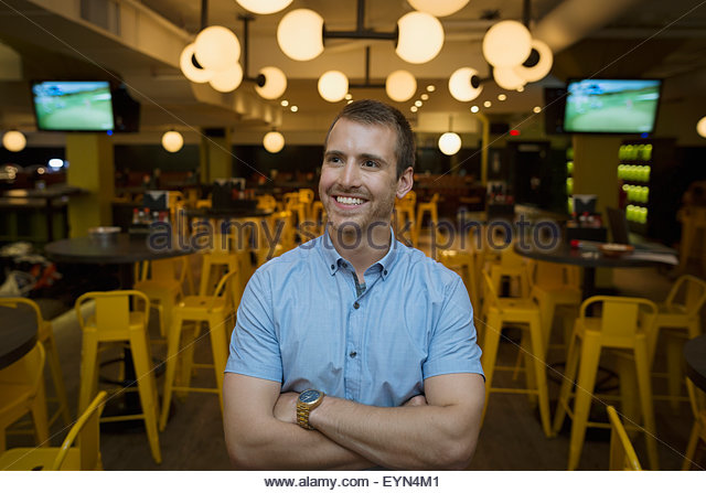 Confident young man in bowling alley bar - Stock Image
