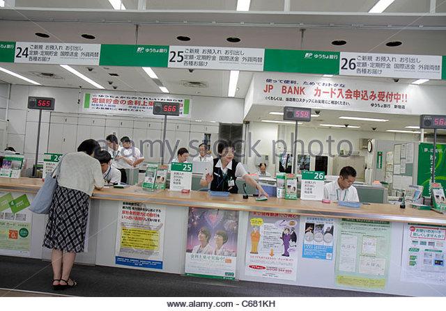 Tokyo Japan Shinjuku Post Office JP Bank kanji hiragana katakana characters symbols Japanese English Asian woman - Stock Image