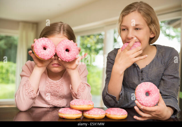 Two sisters one with doughnut holes over her eyes, the other eating - Stock Image