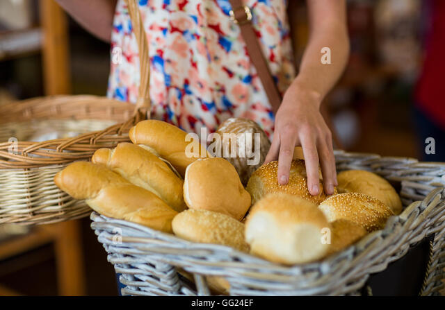 Mid section of woman selecting bread - Stock Image
