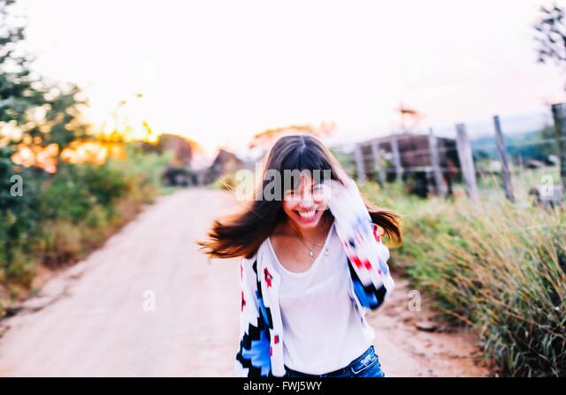 Portrait Of Happy Young Woman Running On Road Amidst Plants Against Clear Sky - Stock Image