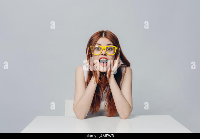 Surprised Caucasian woman sitting at table wearing yellow eyeglasses - Stock-Bilder