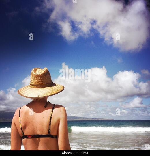 A young women looks out to the surf. Kapalua, Maui Hawaii USA. - Stock Image