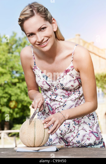 Italy, Tuscany, Magliano, Young woman cutting honey melon, smiling, portrait - Stock Image