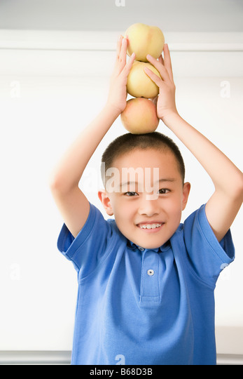 Portrait of a boy balancing apples on his head - Stock Image