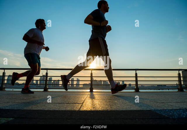 NEW YORK CITY, USA - AUGUST 15, 2015: Silhouettes of men run at sunset on the Hudson River boardwalk at sunset. - Stock-Bilder