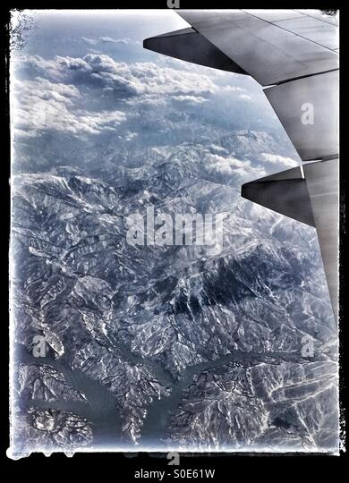 Aerial view of airplane wing, mountains, rivers and clouds as seen from window of airplane. Black vintage frame. - Stock Image