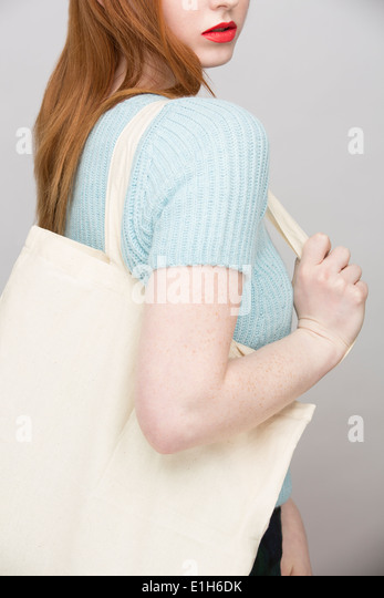 Cropped image of young woman carrying shopping bag - Stock Image