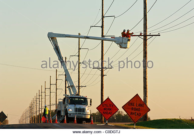 Linemen work on high voltage power lines using a bucket truck in central rural Iowa. USA. - Stock Image