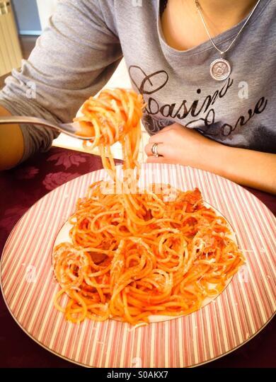 Woman eating spaghetti pasta with tomato sauce - Stock Image