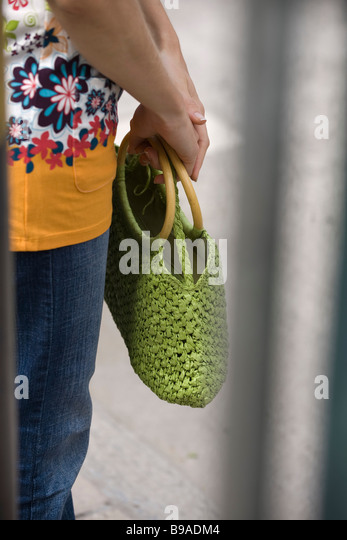 Woman holding handbag, cropped view - Stock Image